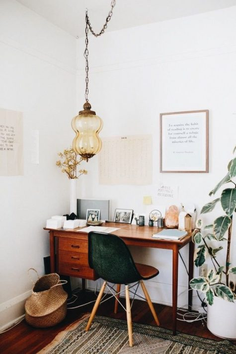 a cozy boho home office nook with a catchy Moroccan lamp, a potted plant, a mid century modern desk, a boho rug and a green chair