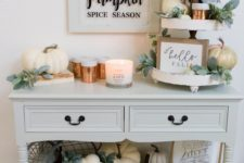 a cozy neutral Thanksgiving console table with lots of natural and faux pumpkins, greenery, candles and signs