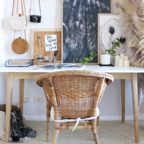 a cozy rustic meets boho home office nook with lot sof artworks, pampas grass, candles and a wicker chair