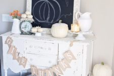 a cozy white console table with a burlap runner, white pumpkins, candles, a chalkboard sign and some neutral pumpkins on the floor