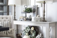 a modern farmhouse console with greenery, white pumpkins, cotton, pinecones and a wreath