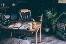 a moody boho home office with a vintage desk and chair, potted plants, a boho rug and ottoman