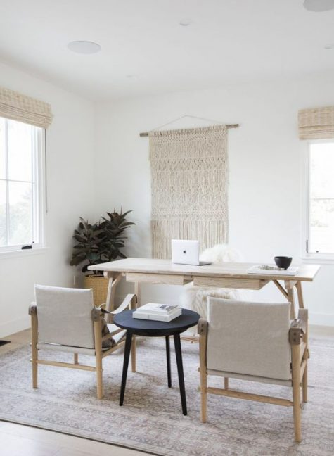 a neutral boho home office with a large macrame wall hanging, a simple wooden desk and neutral chairs plus wicker shades