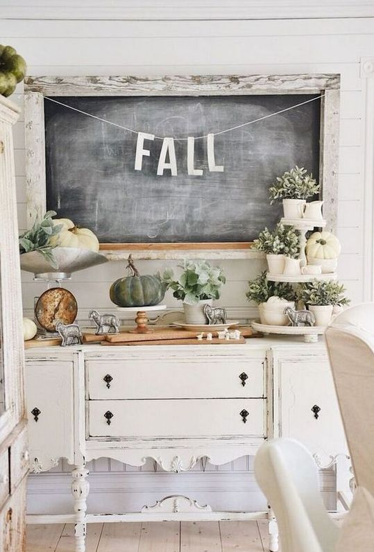 a neutral farmhouse console table with greenery in pots, white pumpkins, smal sheep figurines