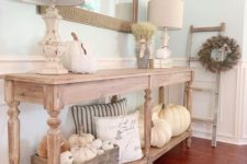 a neutral farmhouse console with white pumpkins, wheat, neutral pillows and a wooden crate