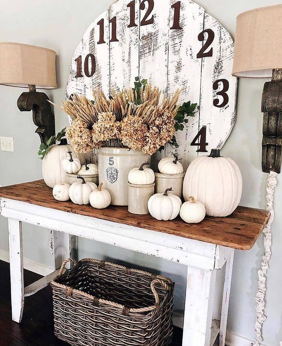 a rustic console table with white pumpkins, dried herbs, a vintage clock and a basket is a chic and cozy idea
