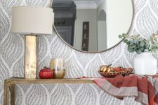 a simple Thanksgiving console table with a plaid blanket, white pumpkins, bright painted ones and a candle