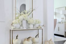 a simple and elegant Thanksgiving console with white blooms, pumpkins and white vases for a chic look
