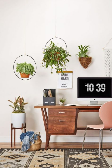 a simple boho meets mid century home office with a stylish wooden desk, a pink chair, a boho rug and suspended planters