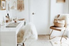 a small and neutral boho home office with a macrame hanging, a leather chair, boho rugs, faux fur and a sleek white desk
