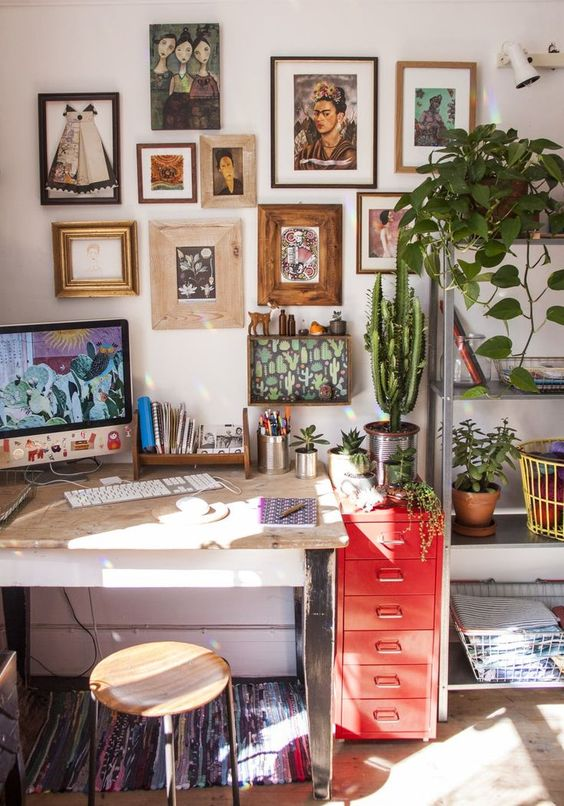 a small yet cozy boho home office with a cool gallery wall, a bright rug and a red chest, los of greenery and cacti