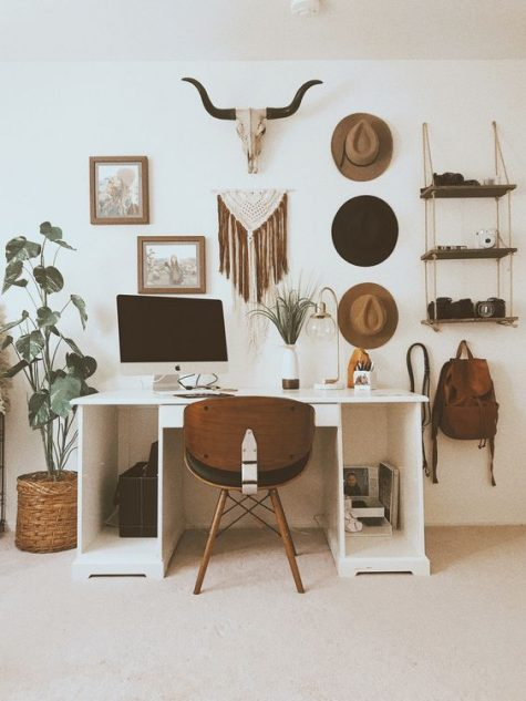 a southwestern boho home office with a macrame hanging, hats, artworks and an animal skull plus a minimal desk and a wooden chair