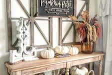 a vintage farmhouse console with white pumpkins, a chalkboard sign, baskets and a floral arrangement