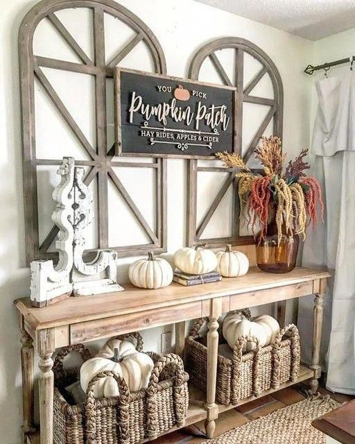 a vintage farmhouse console with white pumpkins, a chalkboard sign, baskets and a floral arrangement