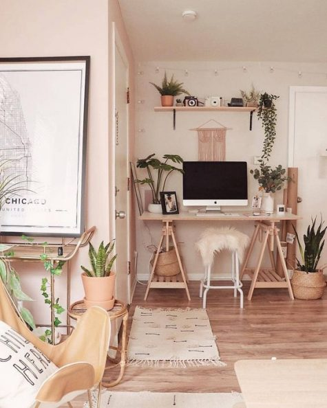 a warm-colored boho space with a wooden trestle desk, an open shelf, potted greenery and plants and long fringe