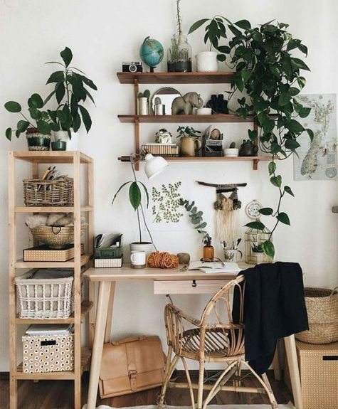 a welcoming boho meets organic home office nook with light-colored wooden furniture, a rattan chair, potted plants and greenery