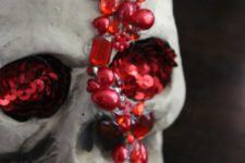 DIY jeweled skull with bright red rhinestones and beads