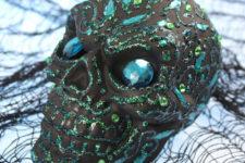 DIY matte black Halloween skull with blue glitter patterns and rhinestones