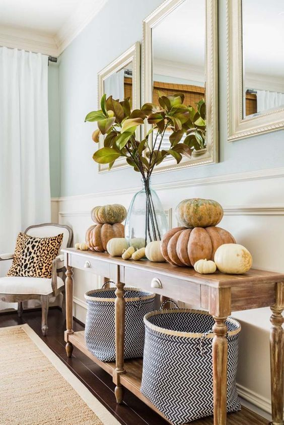 simple and natural Thanksgiving styling with real pumpkins, a foliage arrangement in a clear vase and chevron baskets