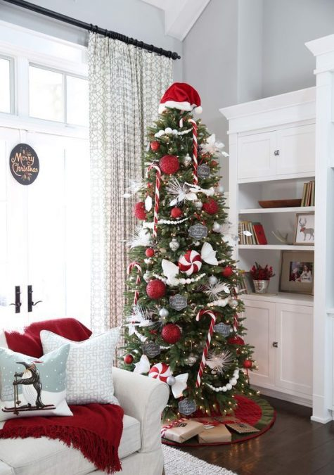 a Christmas tree with lights, red and white ornaments, silver and chalkboard touches plus a Santa cap on top