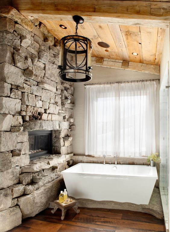 an attic bathroom with a rough stone wall with a fireplace, a pendant lamp and a wooden ceiling for a cozy feel