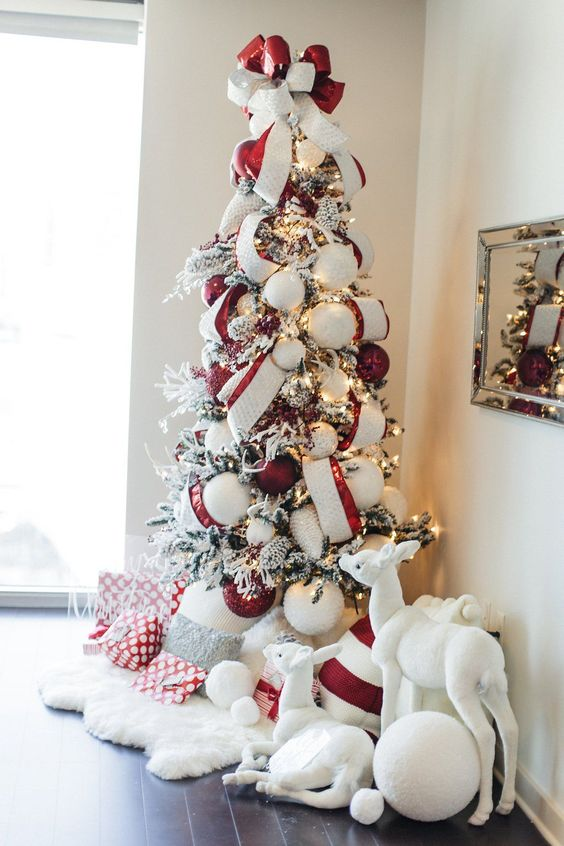 a chic flocked Christmas tree with deep red and white ribbons, oversized ornaments and lights plus pillows and faux fur
