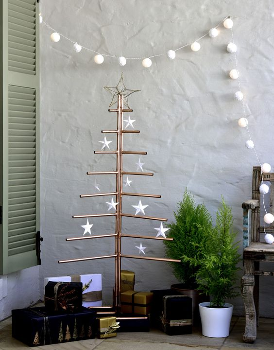 a copper pipe Christmas tree with white star ornaments is a unique and creative alternative to a usual Christmas tree