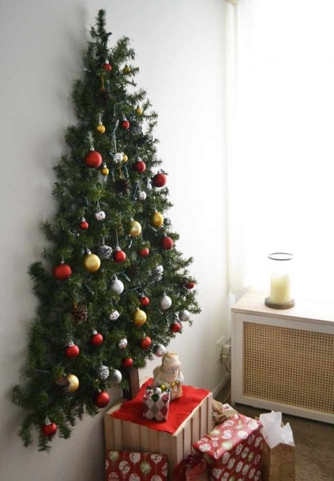 a wall mounted Christmas tree with pine garlands and Christmas ornaments plus pinecones looks natural and cool