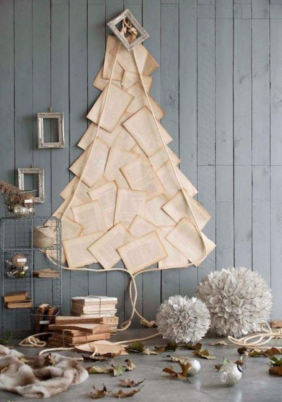 a wall-mounted Christmas tree of vintage book pages and some rope plus a frame on top of it or book lovers
