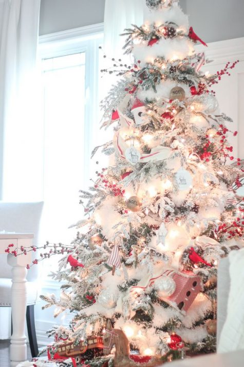 a beautiful flocked Christmas tree with lights, red and white ornaments, red berries and silver touches