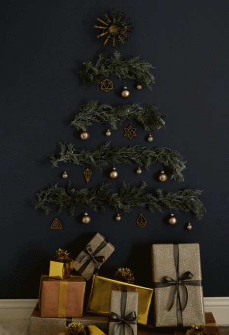 a Christmas tree on the wall made of evergreen branches, lights and dark metallic ornaments