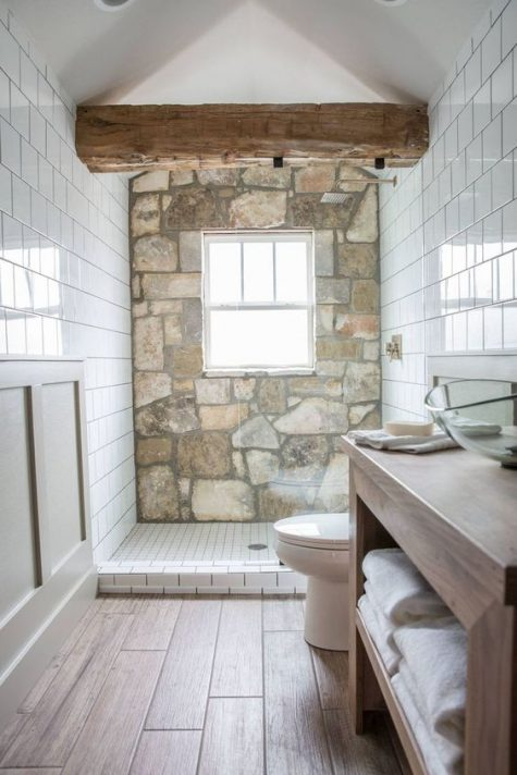 a contemporary bathroom done with wood imitating tiles, white subway ones and a stone wall plus a wooden beam