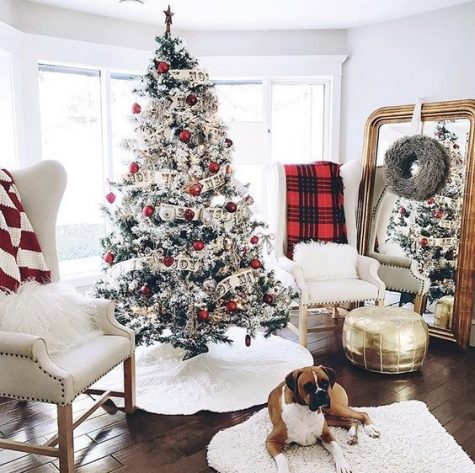 a farmhouse Christmas nook with a flocked tree with red and white ornaments, plaid blankets and white fur