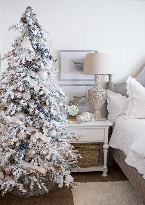 a beautiful flocked Christmas tree with white ribbons, privet berries, metallic ornaments and lights looks really frozen