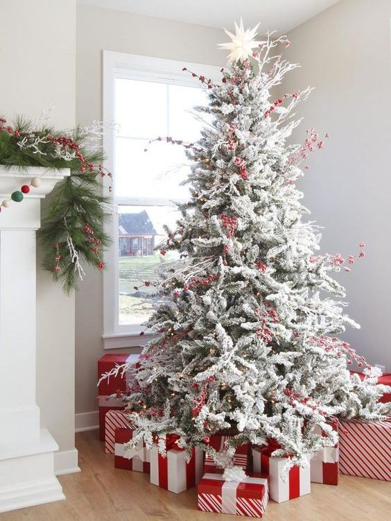 a flocked Christmas tree decorated only with lights and red berries and red and white gift boxes under it