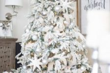 08 a chic flocked Christmas tree with metallic pearly ornaments, stars, striped ribbons and lights