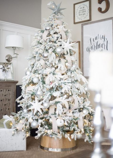 a chic flocked Christmas tree with metallic pearly ornaments, stars, striped ribbons and lights