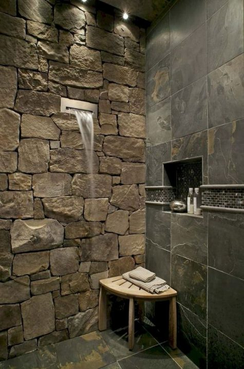 a gorgeous contemporary shower done with a natural stone wall, wall tiles imitating stone and a waterfall shower