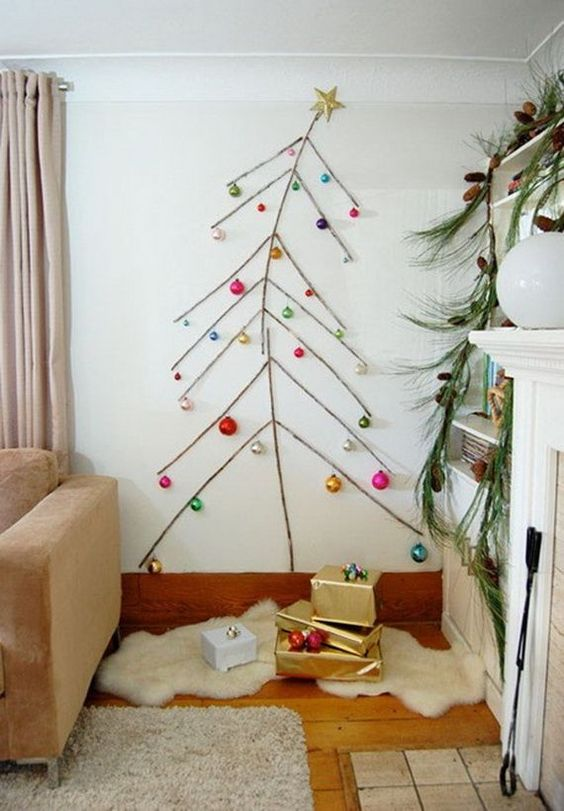 a simple wall Christmas tree done with tape and some colorful ornaments attached to the wall