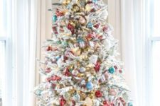 09 a flocked Christmas tree decorated with blue, pink, turquoise and metallic ornaments and lights plus plaid ribbons