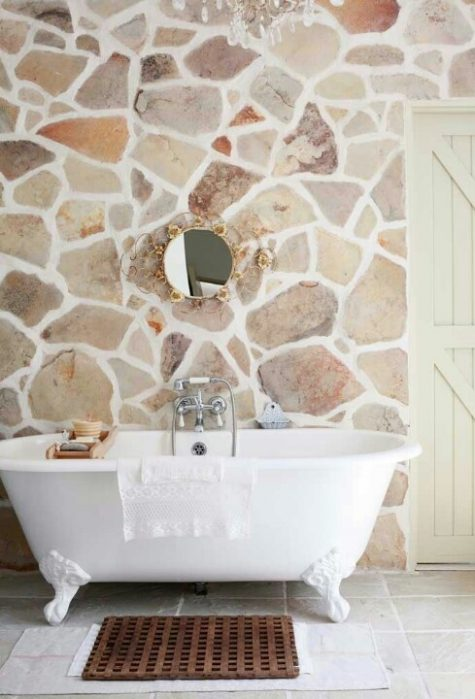 a light-filled farmhouse bathroom with a natural stone wall, a refined mirror and a clawfoot bathtub