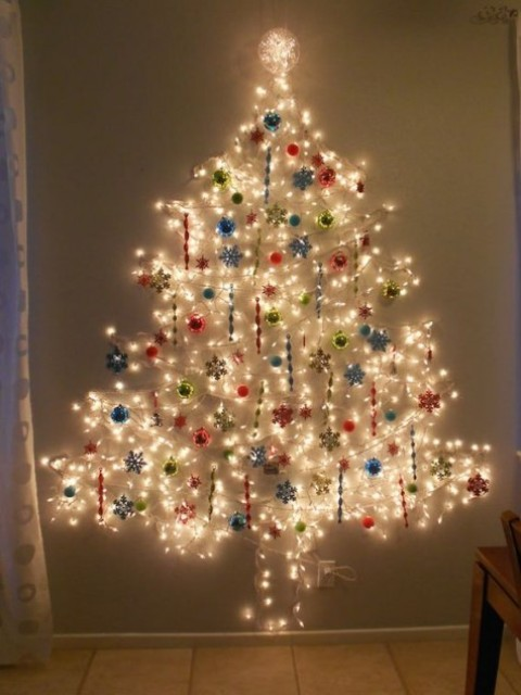 a Christmas tree of lights on the wall with various ornaments   balls and snowflakes in various colors