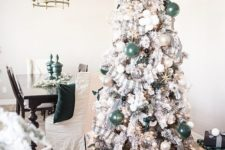 10 a flocked Christmas tree decorated with green, pearly and sheer glass ornaments plus plaid ribbons and eucalyptus