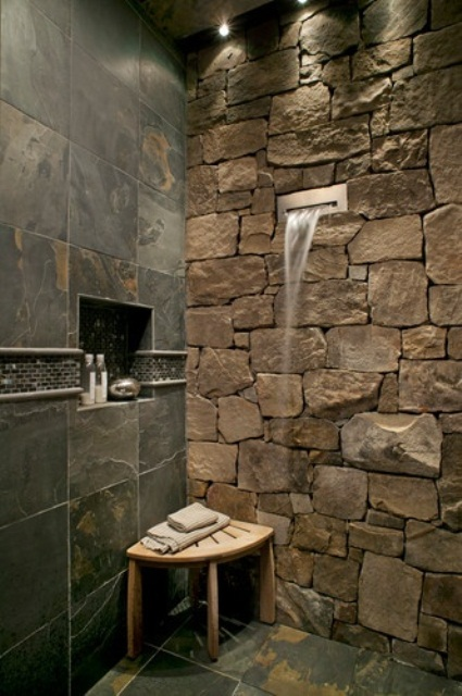 a natural shower space with a stone wall and dark tiles that imitate dark stone, too
