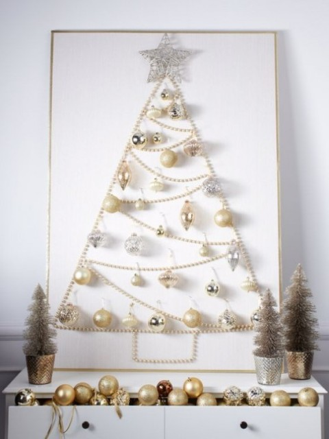 a Christmas tree sign made of pearly and silver ornaments and a pearl garland for a glam space