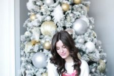 11 a flocked Christmas tree decorated with oversized gold and silver ornaments and snowflakes looks frosted and snowy