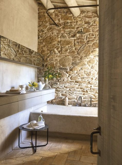 a neutral famrhouse bathroom with a stone wall and a neutral stone bathtub plus wooden beams