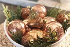 12 a bowl with elegant vintage copper ornaments and evergreens is a simple and chic idea of a holiday centerpiece