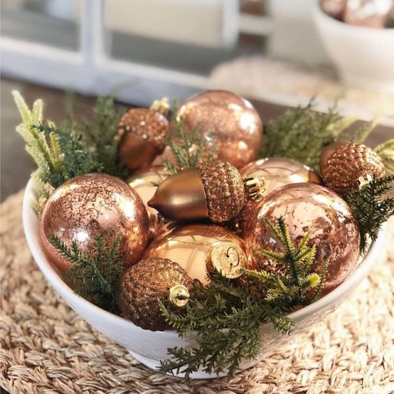 a bowl with elegant vintage copper ornaments and evergreens is a simple and chic idea of a holiday centerpiece