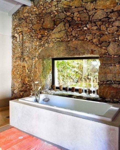 a rough stone wall with a window and a tub placed next to it to make an accent and a statement